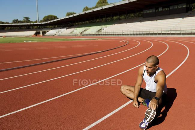 Молодой спортсмен растягивается — стоковое фото