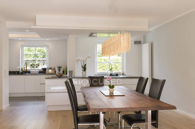 Modern dining area with open plan kitchen in the background — Stock Photo