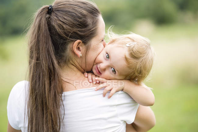 Mother kissing at hugging her little daughter — Stock Photo