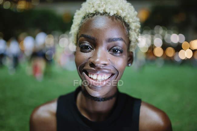 Портрет усміхнений молоду жінку в парку на ніч — стокове фото