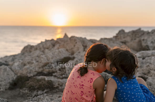 Two little sisters sitting at rocky coast at sunset — Stock Photo