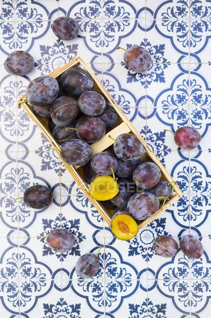 Vue de dessus du panier de l'attelle de prunes sur tiels — Photo de stock