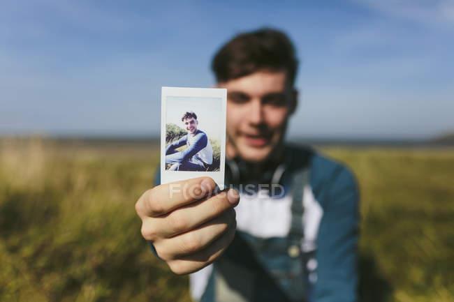 Man showing polaroid photo — Stock Photo