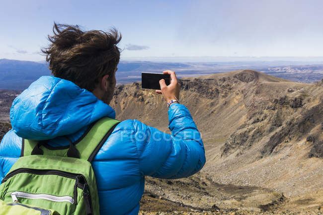 Hiker taking photo with smartphone — Stock Photo
