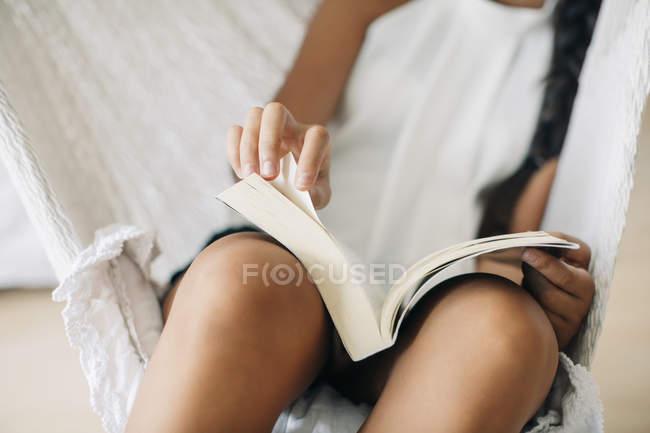Жінка сидить в гамаку і читання книги — стокове фото