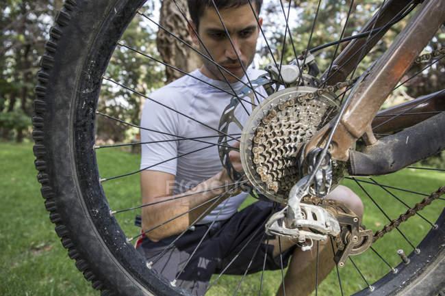 Чоловік вивчає і коригує колесо гірського велосипеда — стокове фото