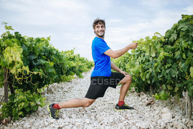 Man doing stretching in a vineyard — Stock Photo