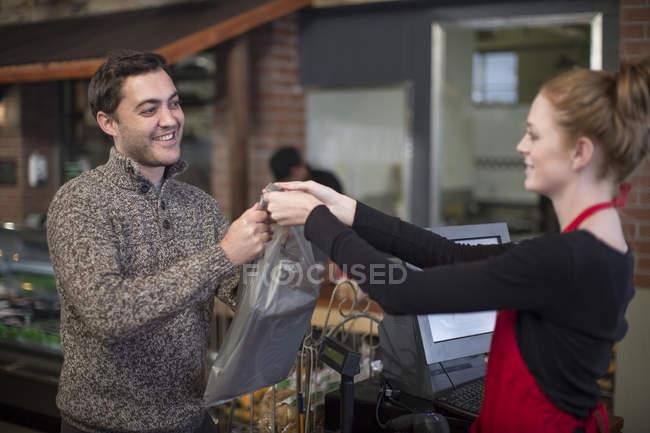 Продавец, сдача мешок для клиентов в магазине — стоковое фото