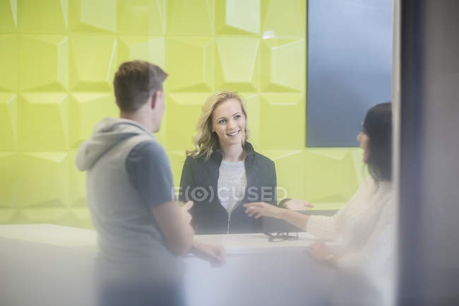 Receptionist talking to clients — Stock Photo
