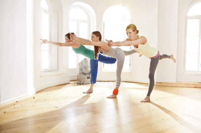 Three women in sunny yoga studio holding Virabhadrasana pose — Stock Photo