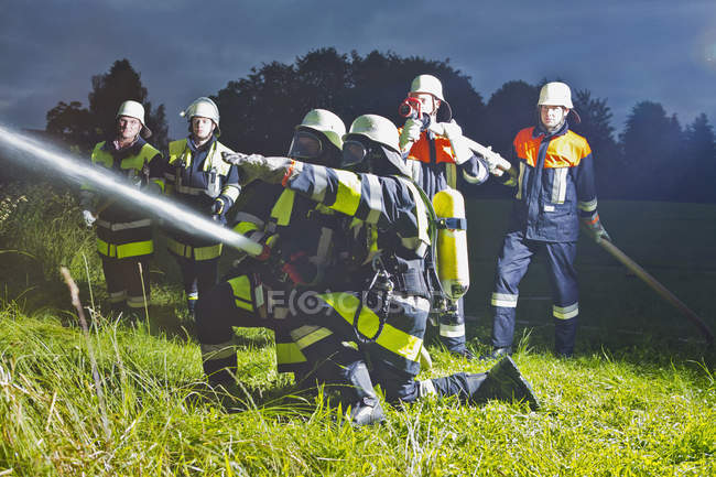 Fire brigade working in nature at dusk — Stock Photo