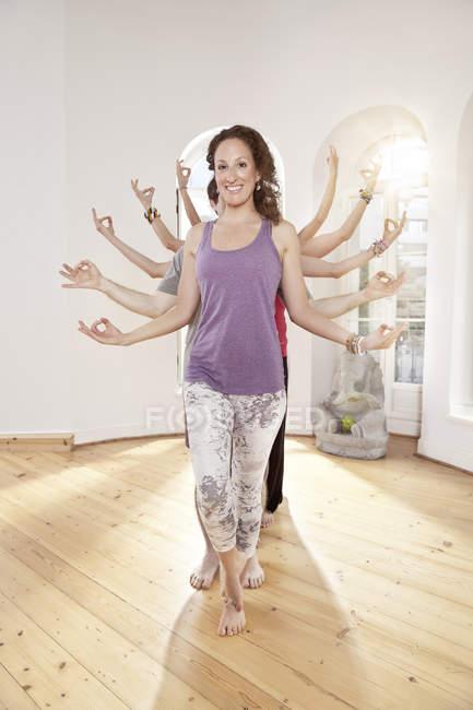 Groupe d'yoga personnes formant les bras comme les mains de la déesse plusieurs bras — Photo de stock