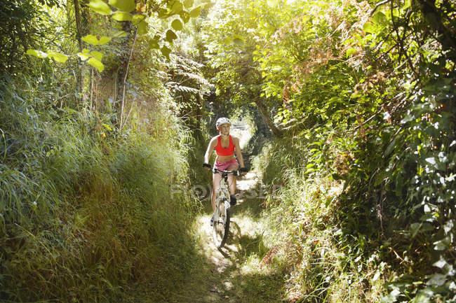 Молодая женщина, езда Горный велосипед тропа — стоковое фото