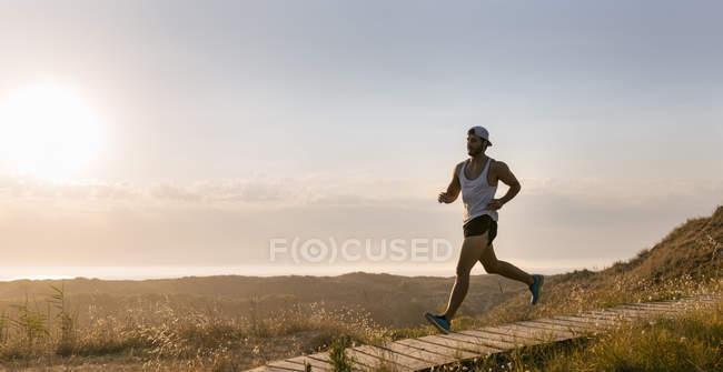 Іспанія, Авілес, спортсмен людина біжить вздовж прибережних стежок на заході сонця — стокове фото
