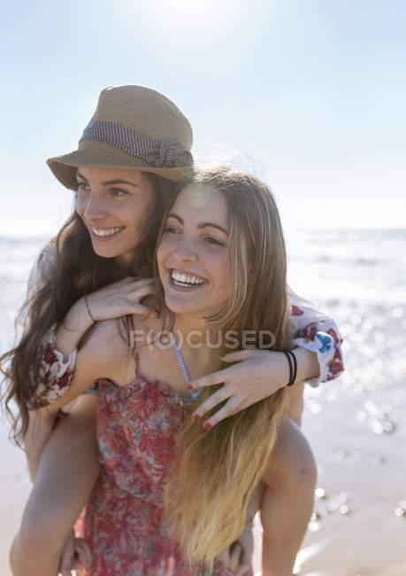 Glücklich Teenager-Mädchen geben ihre beste Freundin eine Huckepack Fahrt am Strand — Stockfoto