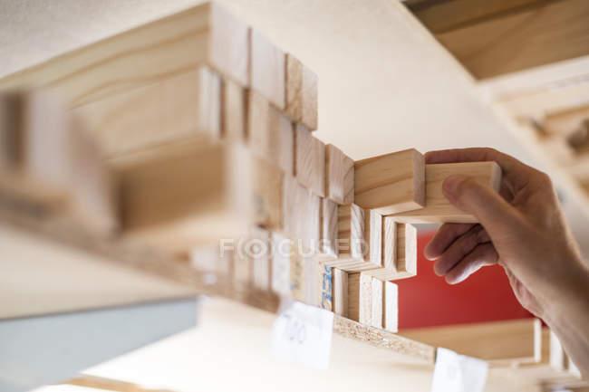 Рука, приймаючи дерев'яному каркасі з полиці в полотні майстерні — стокове фото
