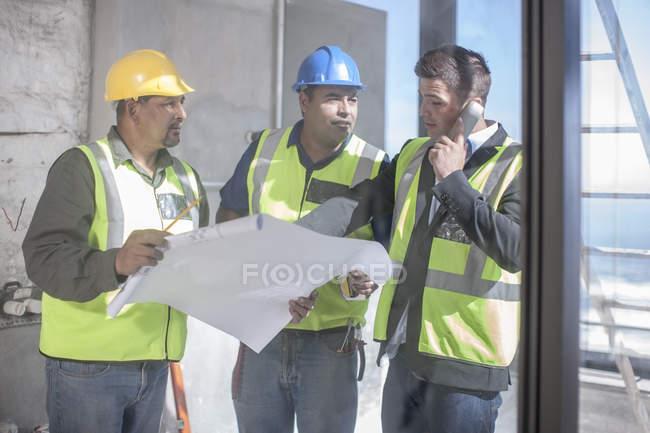 Архітектор і будівельних робітників, обговорення план будівництва — стокове фото