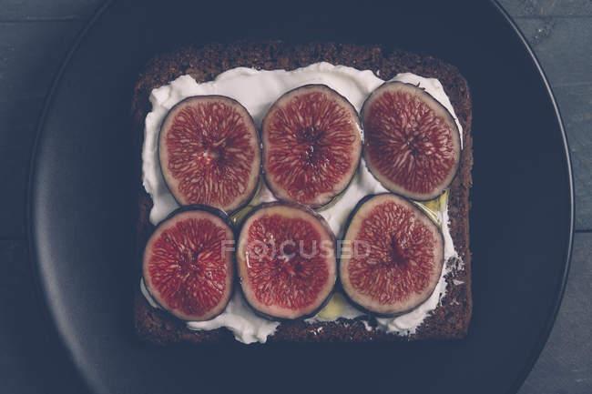 Поджаренный ржаной хлеб со сливочным сыром, нарезанным инжиром и оливковым маслом на черной тарелке — стоковое фото