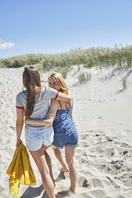 Two female friends walking arm in arm on the beach, rear view — Stock Photo