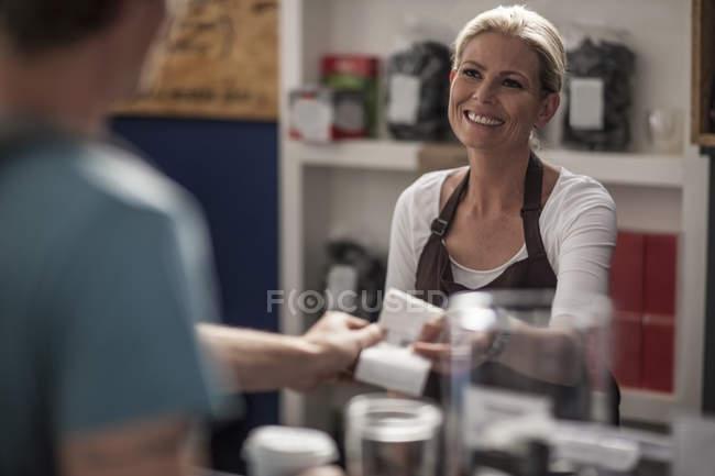 Женщина в кафе передачи получения клиента — стоковое фото