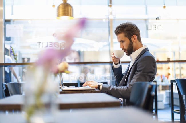 Businessman drinking coffee and using laptop in cafe — Stock Photo