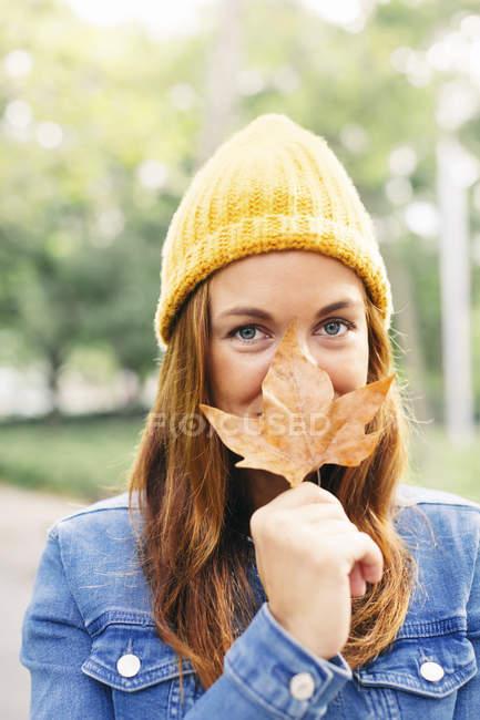 Портрет улыбающийся рот покрытием молодая женщина с осенних листьев — стоковое фото