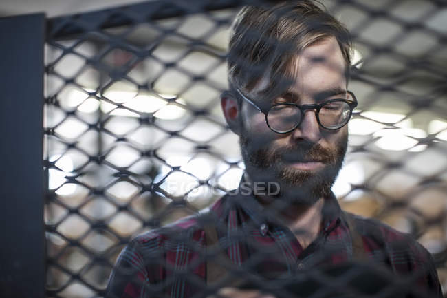 Portrait of concentrated man in workshop behind grid — Stock Photo