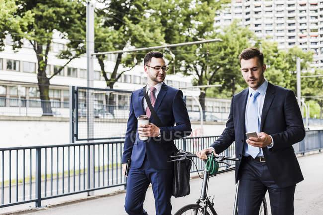 Hommes d'affaires marchant à vélo — Photo de stock