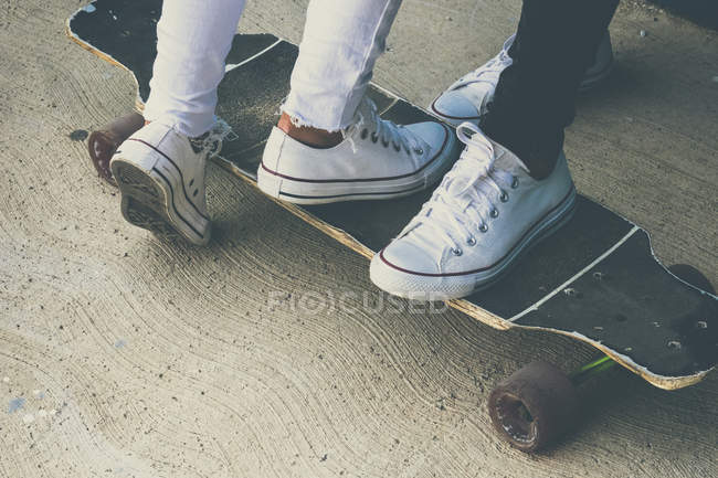 Feet of two teenagers on skateboard — Stock Photo