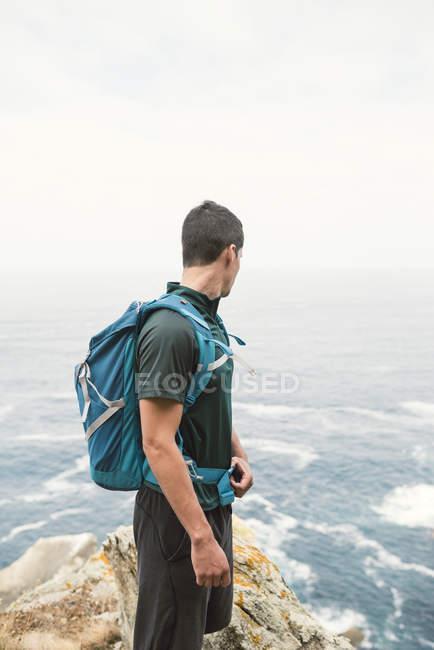 Giovane con uno zaino di fronte al mare sulla costa — Foto stock