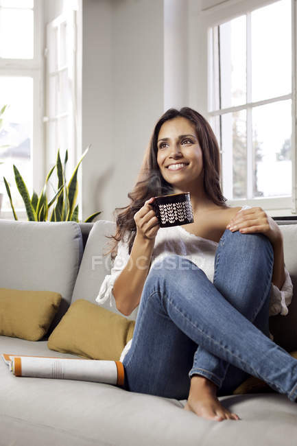 Smiling Woman Relaxing On Couch Holding A Mug Color Image Toothy Smile Stock Photo 173718862