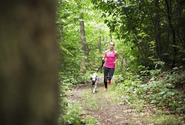 Giovane donna che fa jogging con cane nella foresta — Foto stock