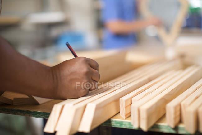 Человек в холсте, маркирующий кусок дерева карандашом — стоковое фото