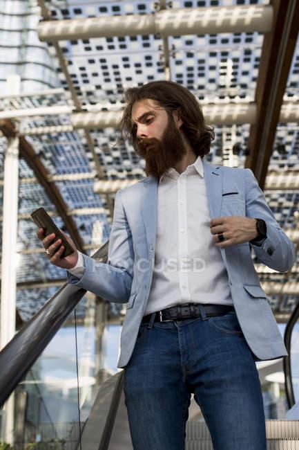 Бизнесмен, использующий мобильный телефон — стоковое фото
