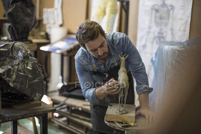 Sculptor working in studio on animal figurine — Stock Photo