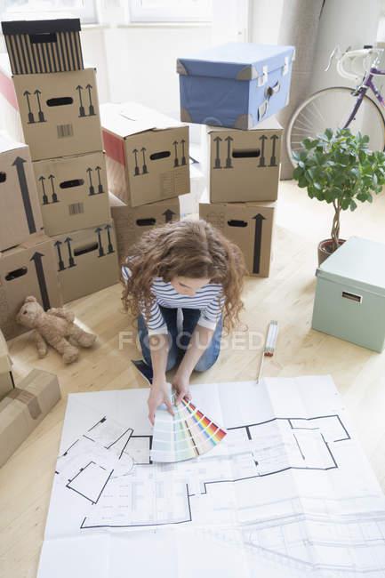 Mulher cercada por caixas de papelão com amostras de cores e plano de construção no chão — Fotografia de Stock