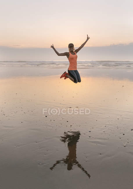 Young athlete woman jumping on the beach in the evening — Stock Photo