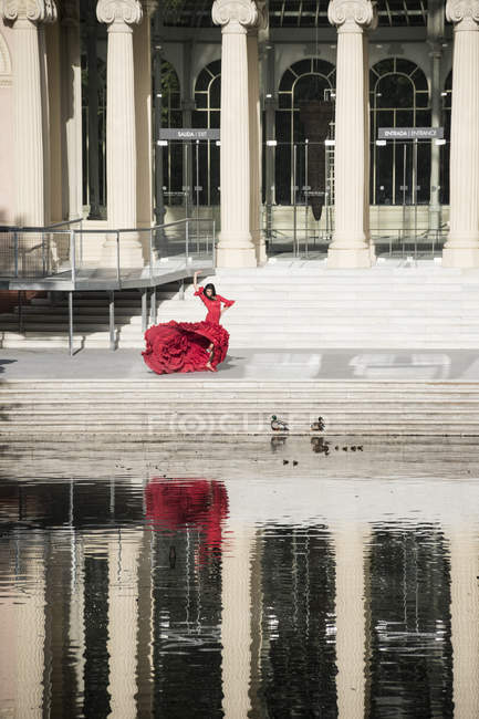 Женщина в красном фламенко на террасе — стоковое фото