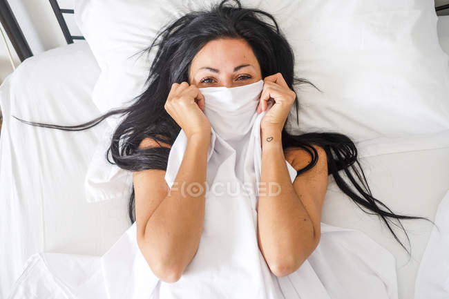Woman lying in bed, obscured face — Stock Photo