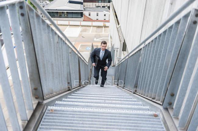 Businessman walking upstairs — Stock Photo