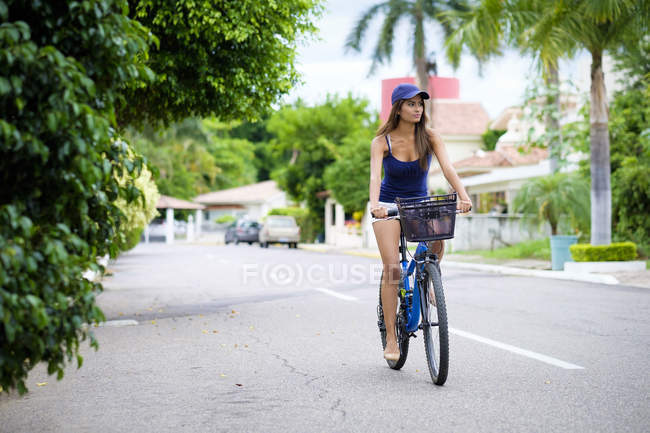 México, Nayarit, jovem mulher andando de bicicleta na rua — Fotografia de Stock