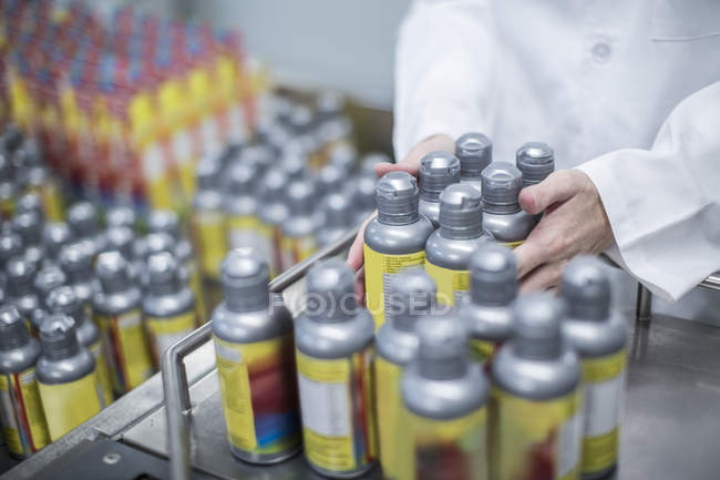 Worker with spray bottles in medical factory — Stock Photo