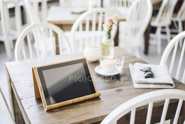 Digital tablet, sunglasses, newspaper and cup of coffee — Stock Photo