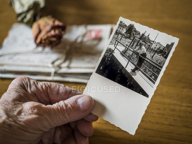 Old woman holding picture of her boyhood friend in hand, old letters and dried rose — Stock Photo