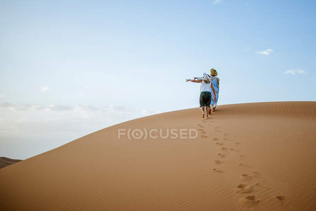 Berber man and woman tourist walking in the desert, pointing to the left — Stock Photo