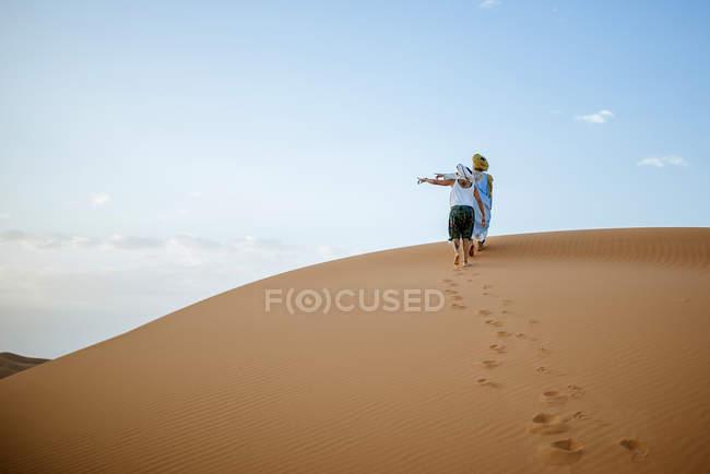 Berber Mann und Frau Touristen gehen in der Wüste, der nach links zeigt — Stockfoto
