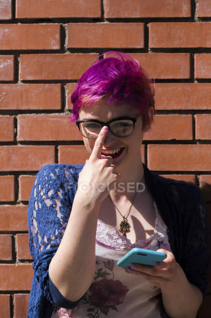 Portrait of laughing young woman with dyed hair adjusting her glasses — Stock Photo