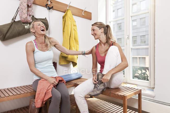 Two young women having fun in yoga studio changing room — Stock Photo