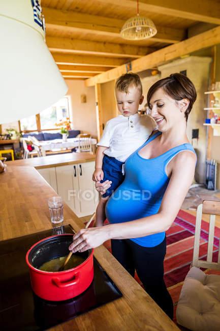 Беременная мать готовит, вынашивая сына. — стоковое фото