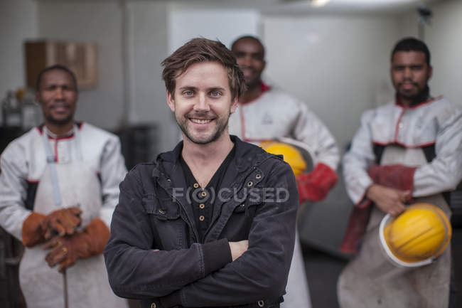 Portrait of smiling man standing in front of staff — Stock Photo
